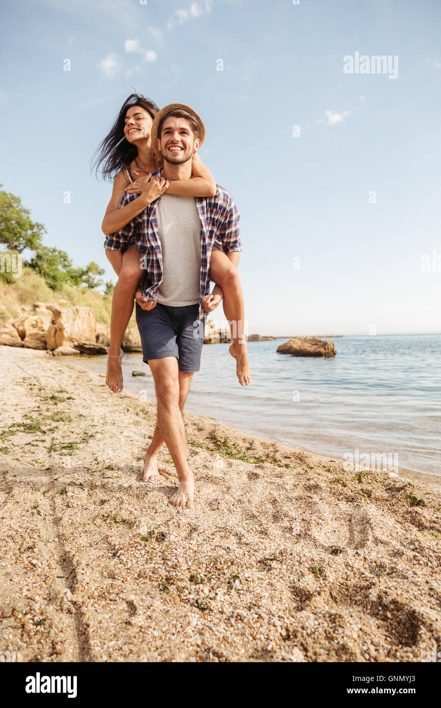 Handsome smiling young man giving piggy back ride à sa petite amie à la plage Photo Stock