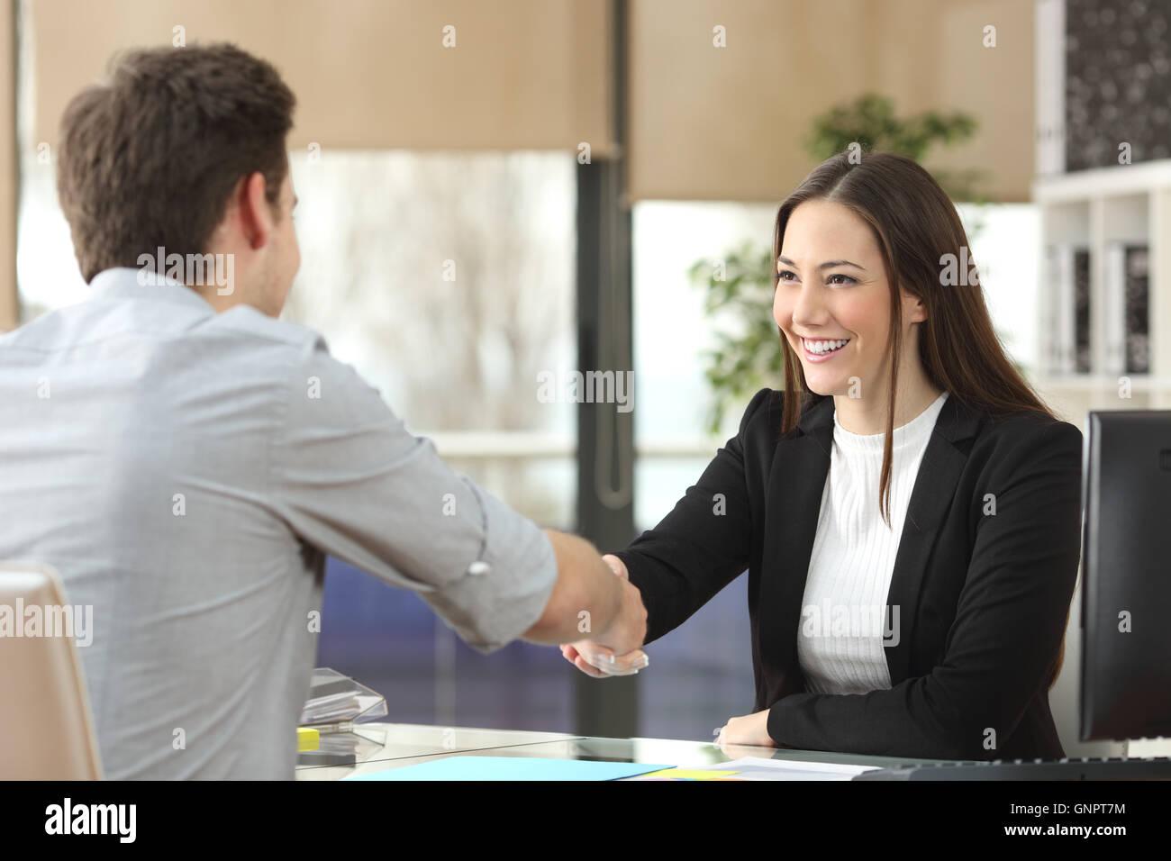 Happy businesswoman handshaking avec client fermeture de la transaction dans un bureau intérieur avec une fenêtre Photo Stock