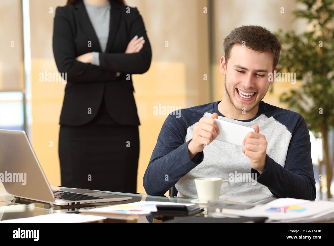 Employé paresseux de jouer avec son smartphone assis dans un bureau pendant que son patron est en colère Photo Stock