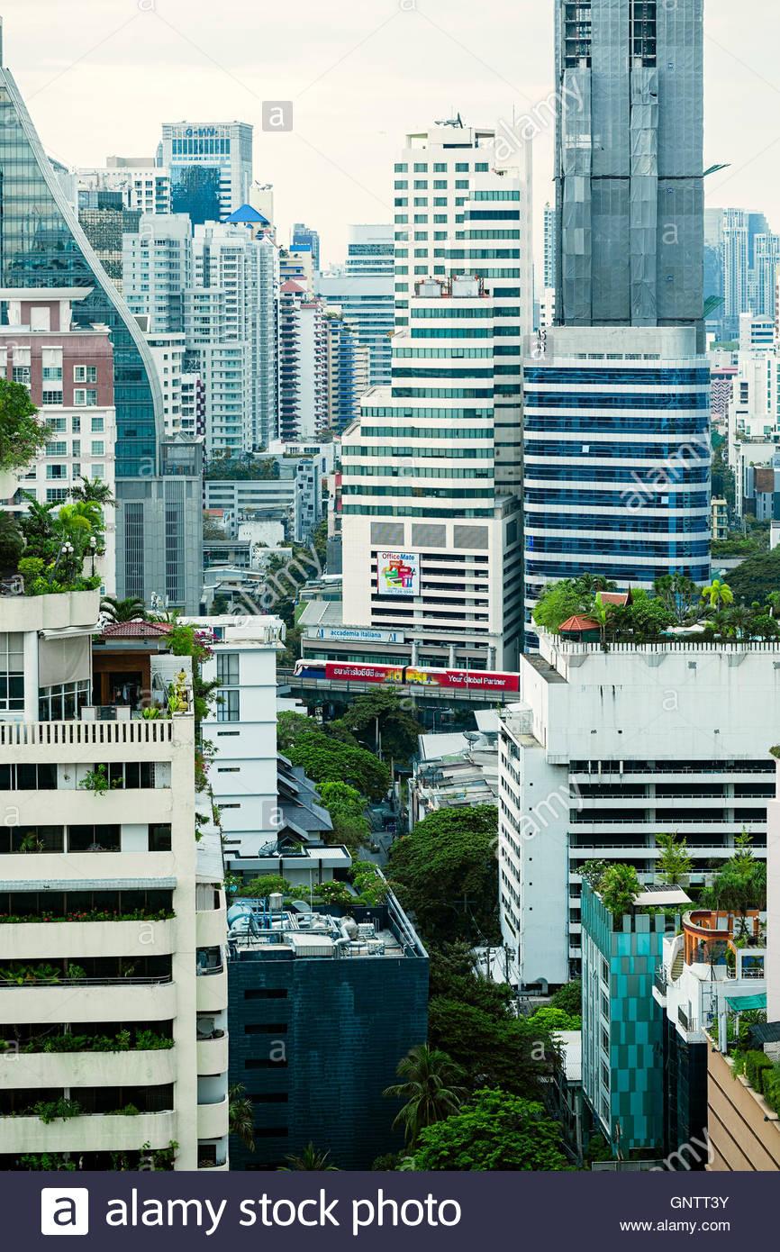 Vue de l'Aérotrain de passage entre des gratte-ciel à Bangkok Photo Stock