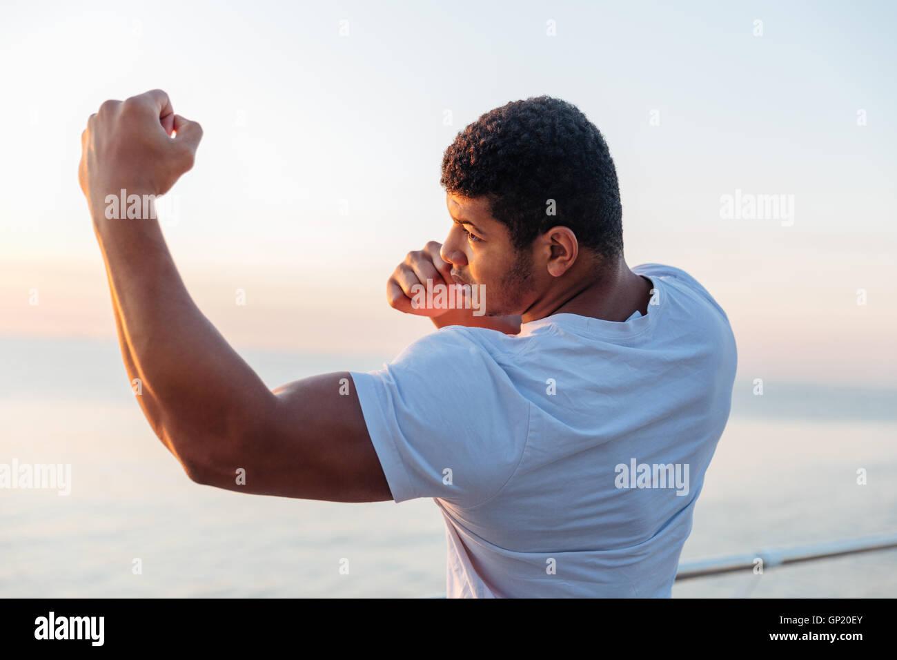 Jeune homme afro-américain musculaire permanent de l'athlète et la pratique de la boxe de l'ombre à l'extérieur Banque D'Images