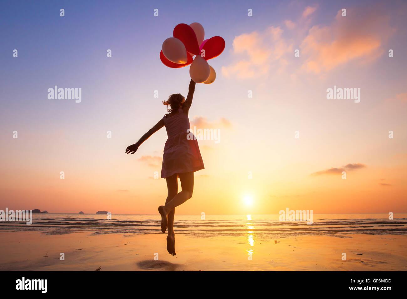Imagination, happy girl jumping avec ballons multicolores au coucher du soleil sur la plage, fly, suivez votre rêve Photo Stock