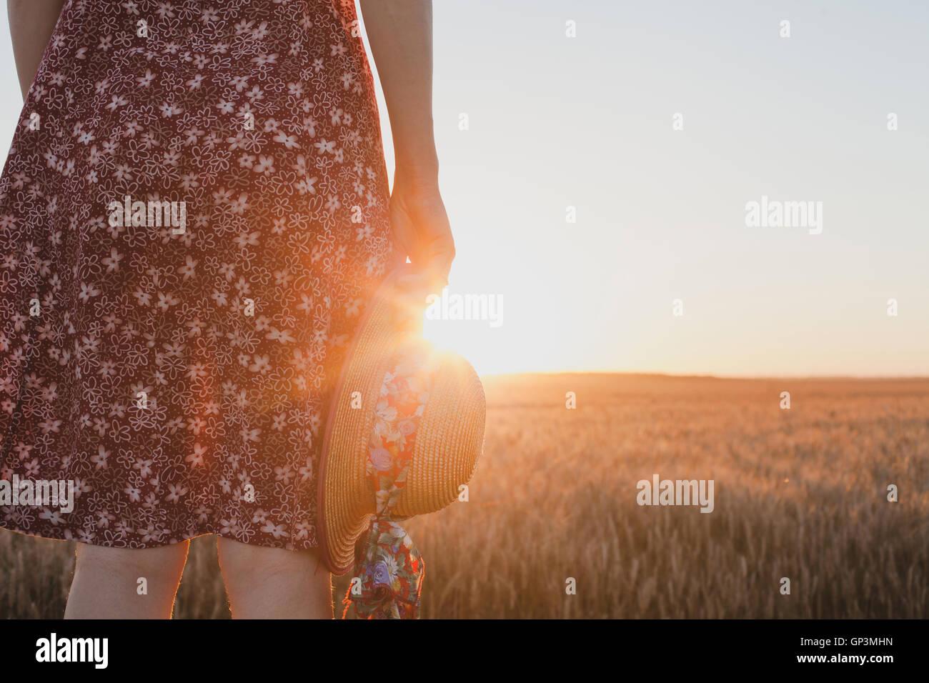 Concept d'attente ou d'adieu, le coucher du soleil, d'été femme hand holding hat Photo Stock