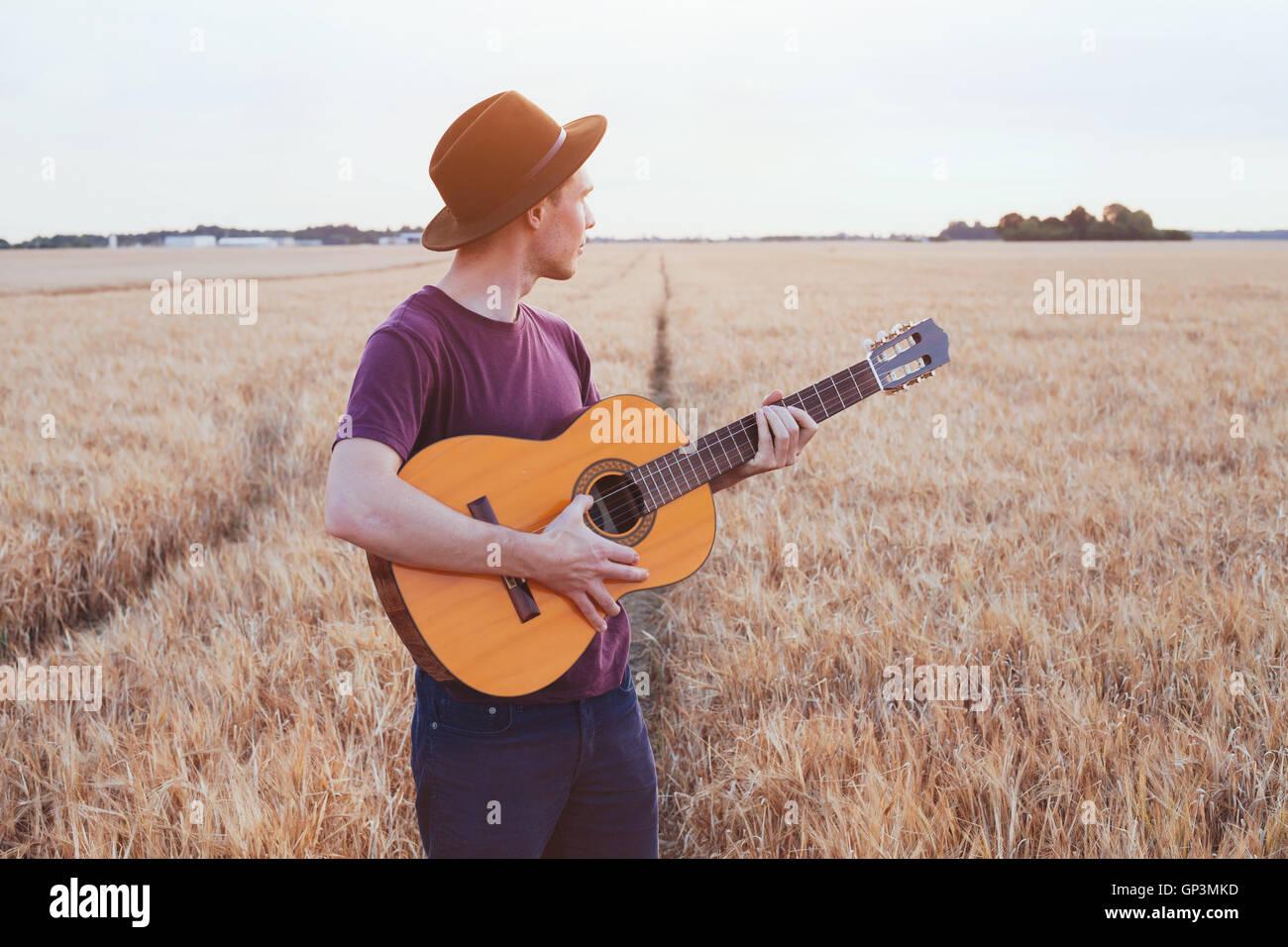 Jeune homme jouant de la guitare dans le domaine au coucher du soleil, l'amour romantique chanson Photo Stock