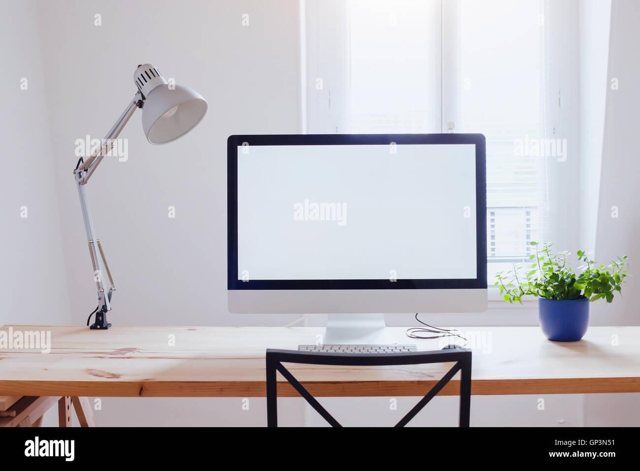 Au milieu de beau bureau moderne ordinateur avec écran vide vide