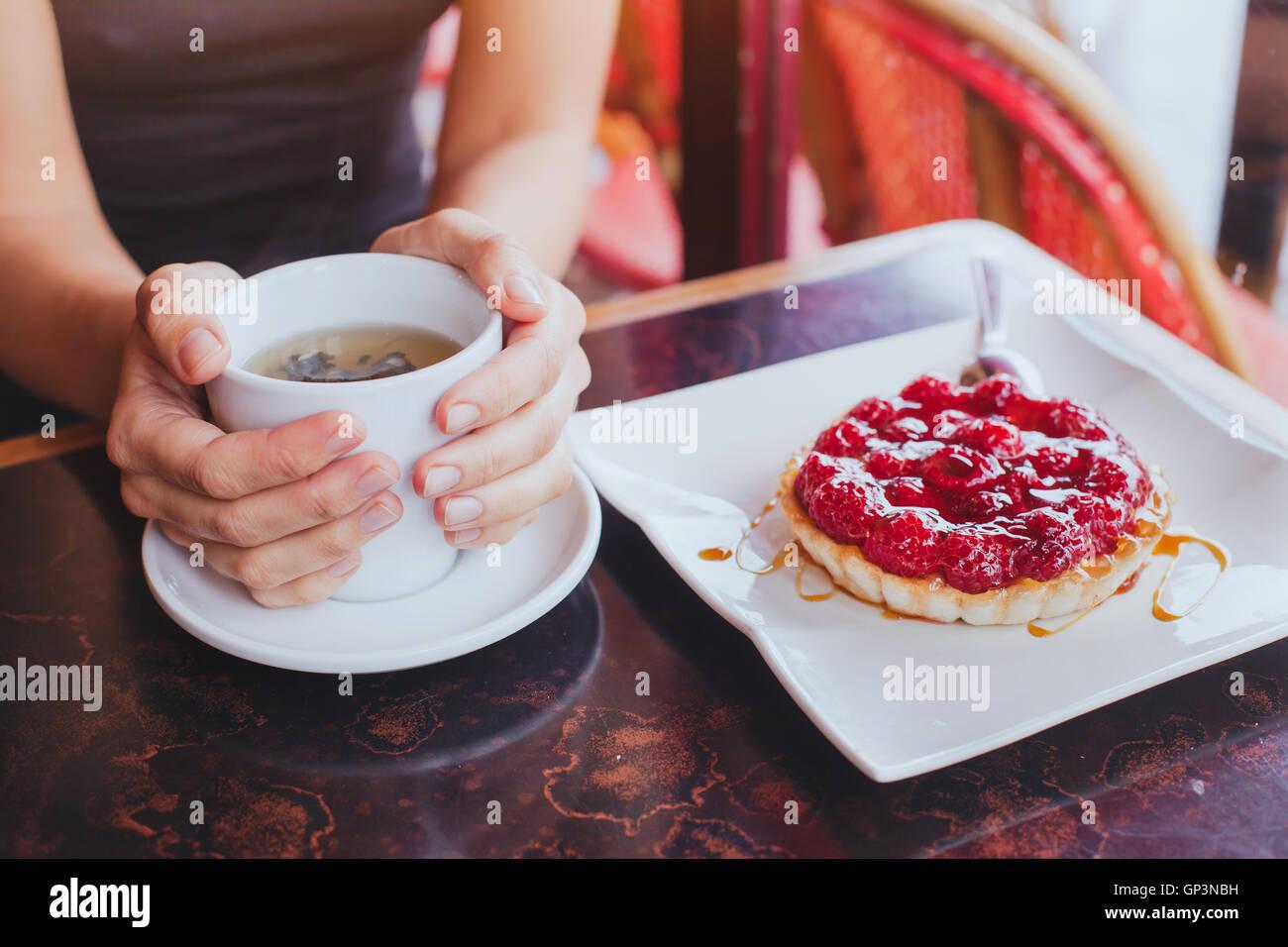 Boire le thé avec dessert sucré en cafe, Close up of hands avec cuvette et un gâteau aux fruits Photo Stock