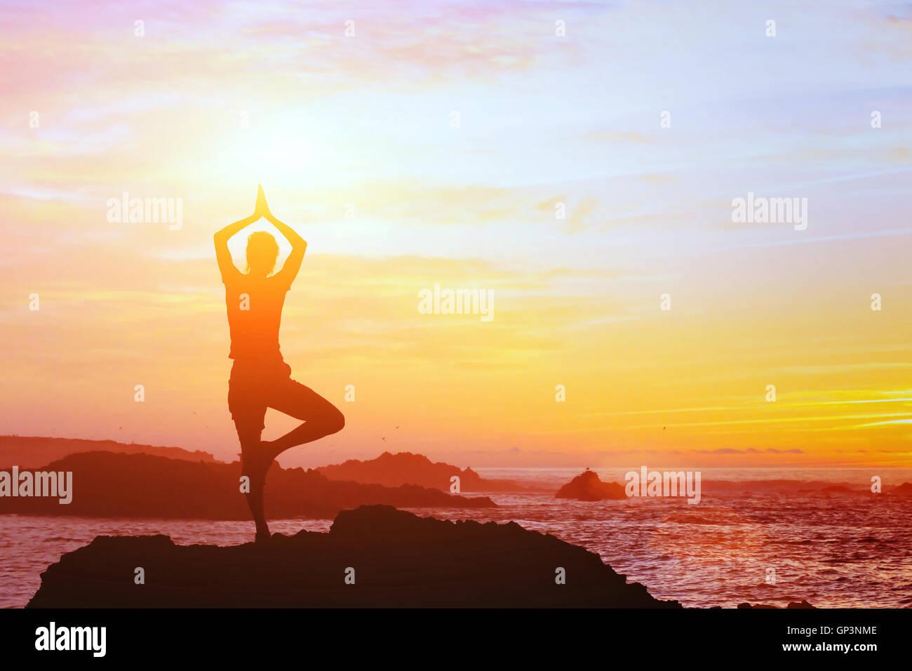 Beau fond yoga, silhouette de femme sur la plage au coucher du soleil, la pleine conscience Photo Stock
