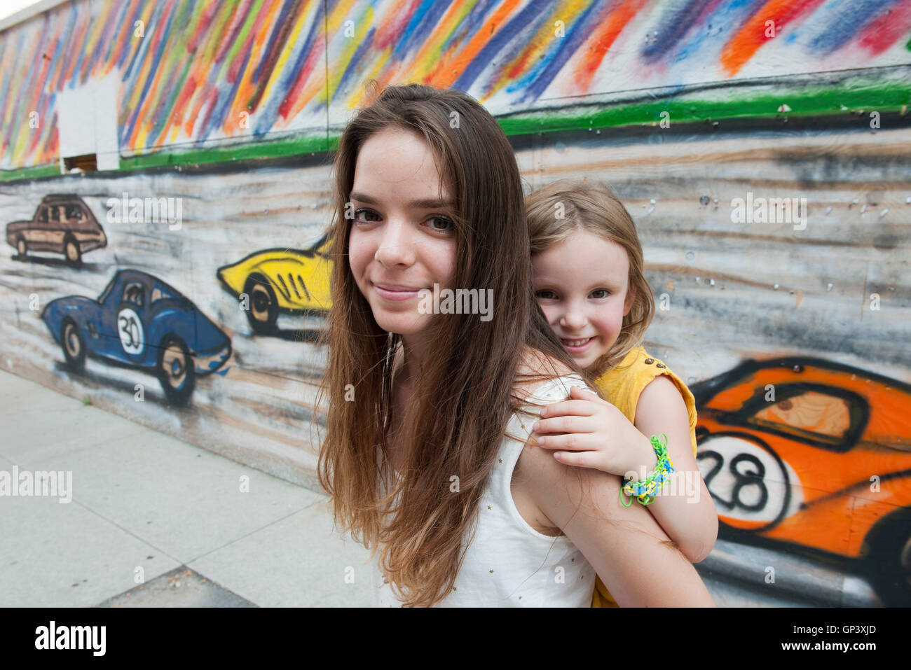 Teenage girl giving sa petite sœur un piggyback ride, portrait Banque D'Images