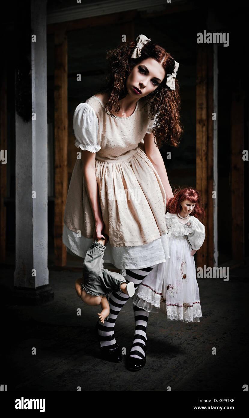 L'étrange fille effrayante avec des poupées dans les mains Photo Stock