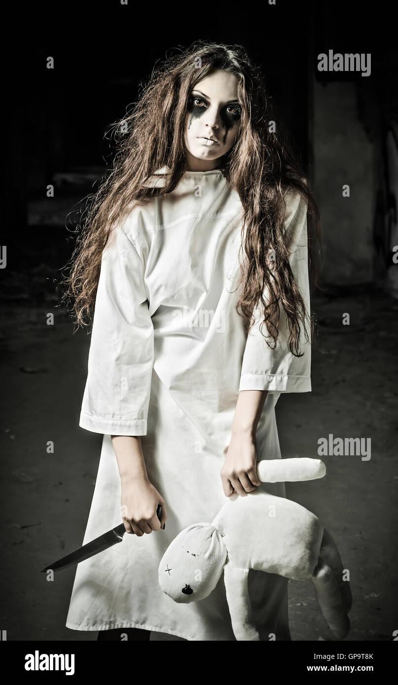 Style horreur shot: une étrange jeune fille triste avec moppet doll et couteau en mains Banque D'Images