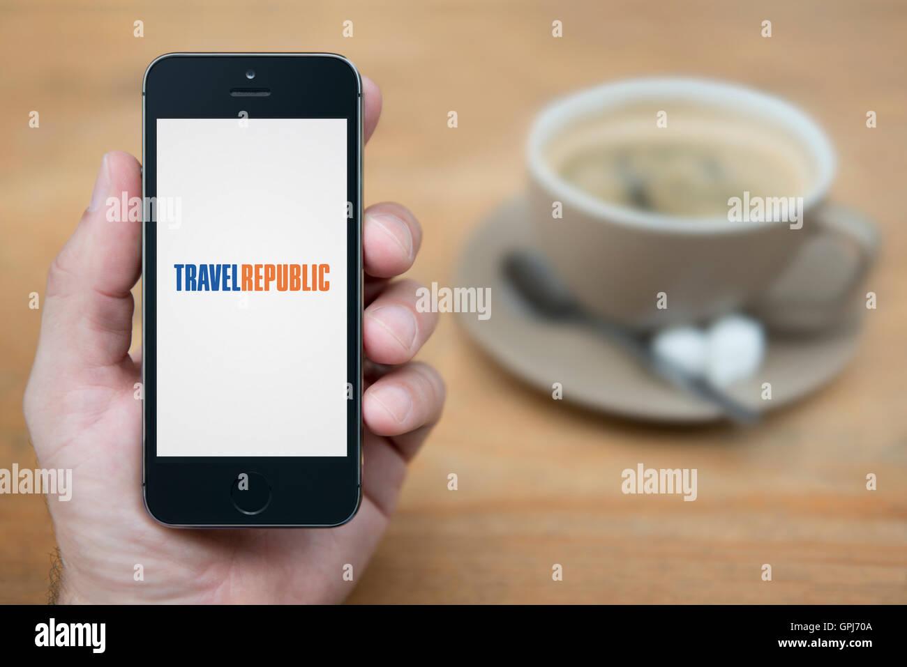 Un homme se penche sur son iPhone qui affiche le logo République Voyage, alors qu'assis avec une tasse Photo Stock