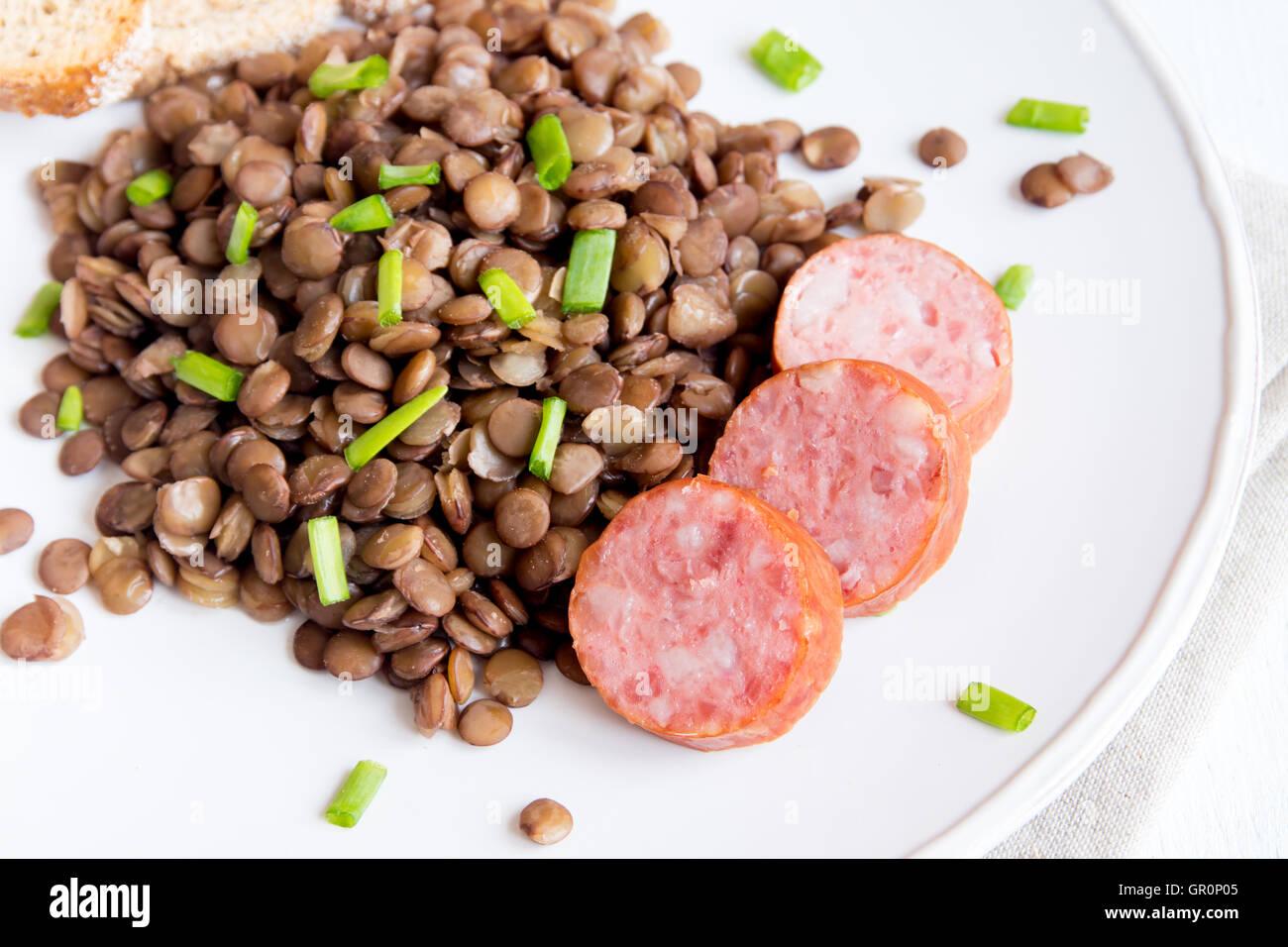 Lentilles vertes avec saucisse de porc (cotechino) on white plate Photo Stock