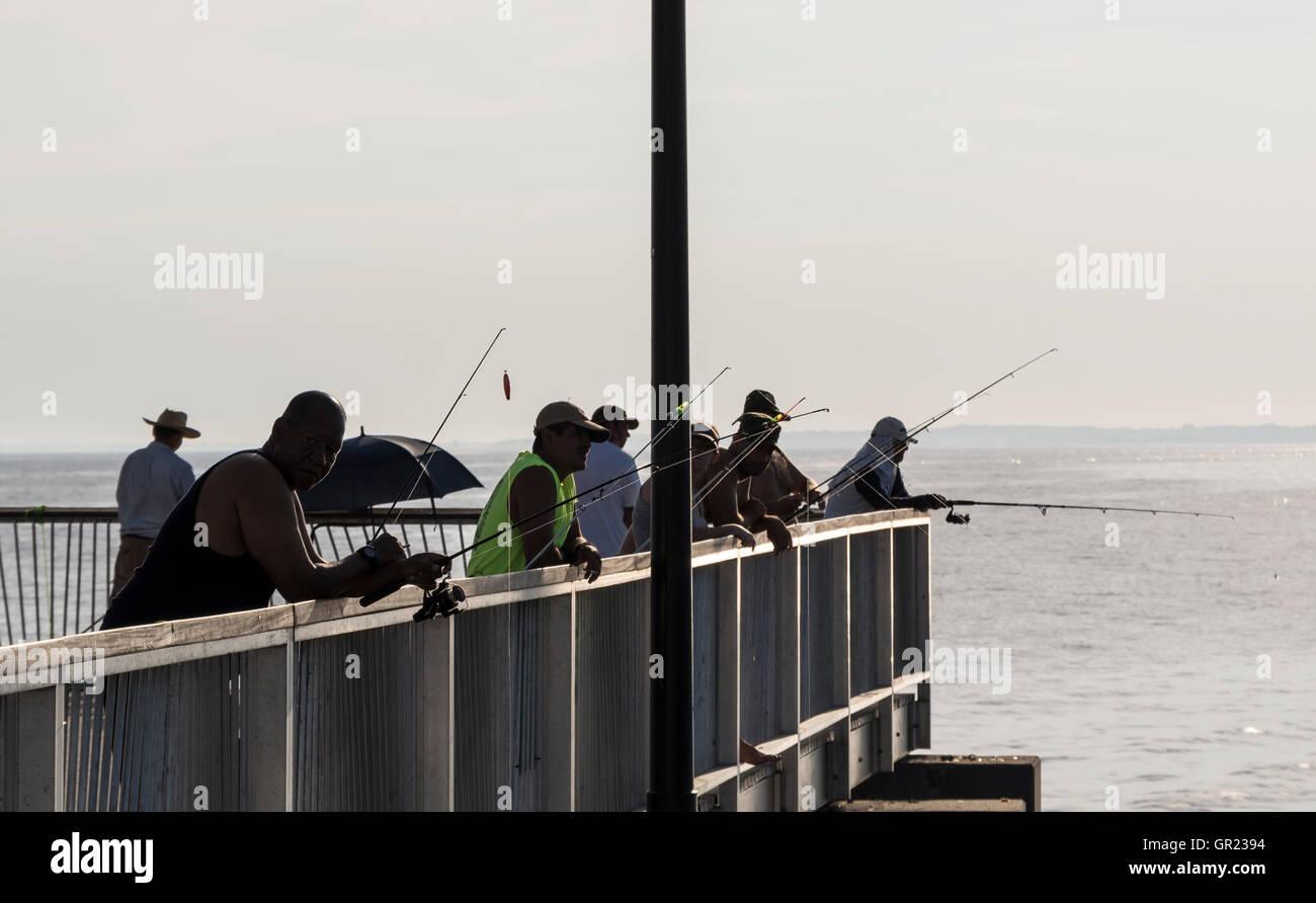 Pêche Les pêcheurs avec tiges à partir de la fin d'un pier at sunset Photo Stock