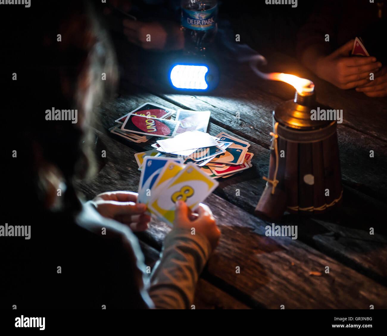 Les enfants jouent le jeu de carte Uno par une bougie d'huile tout en camping à French Creek State Park Photo Stock