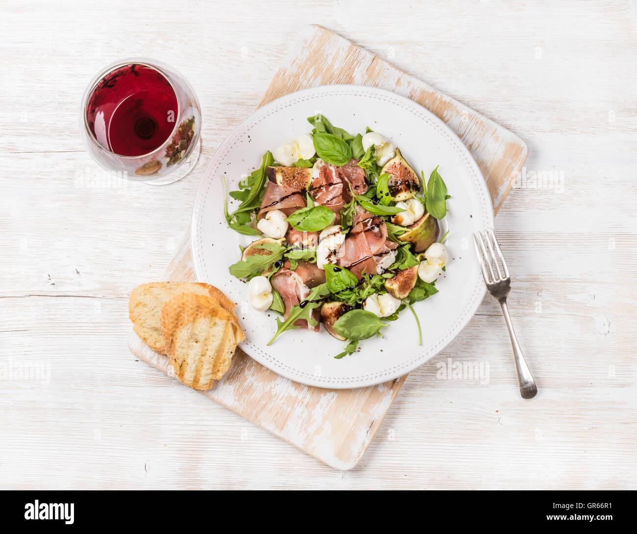 Le prosciutto, roquette, salade de figues avec du pain et verre de vin rouge Photo Stock