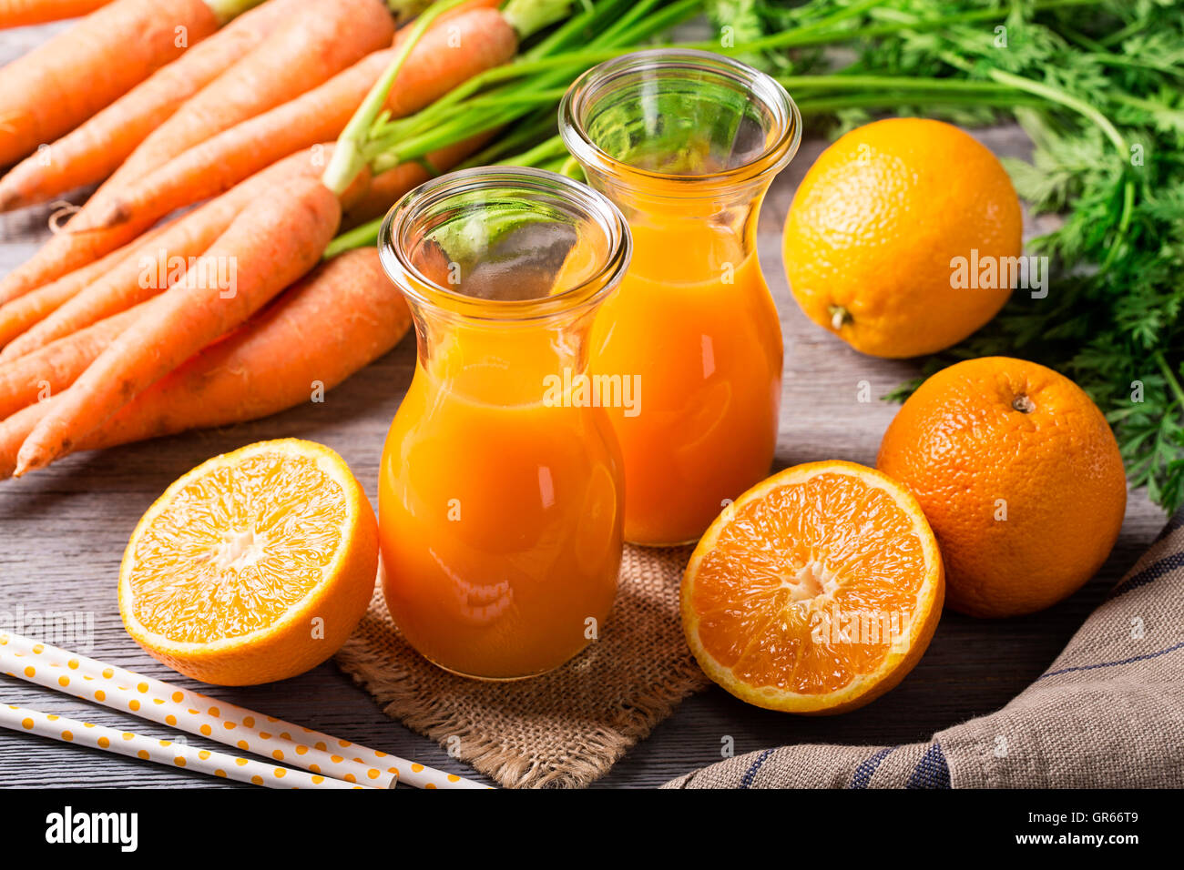 Carotte jus d'orange sur fond de bois Photo Stock