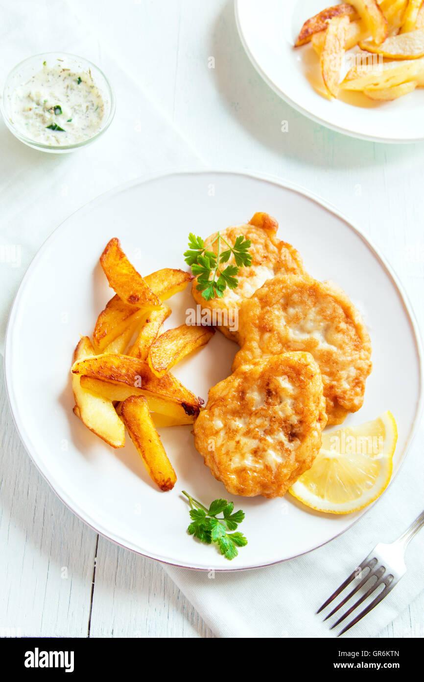Des croquettes de poisson avec frites sur plaque blanche close up Photo Stock