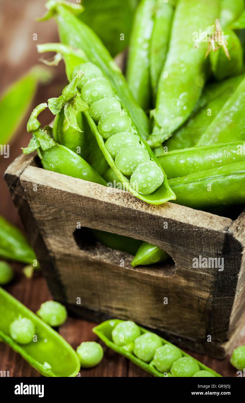 Pois verts frais mûrs dans un coffret en bois Banque D'Images