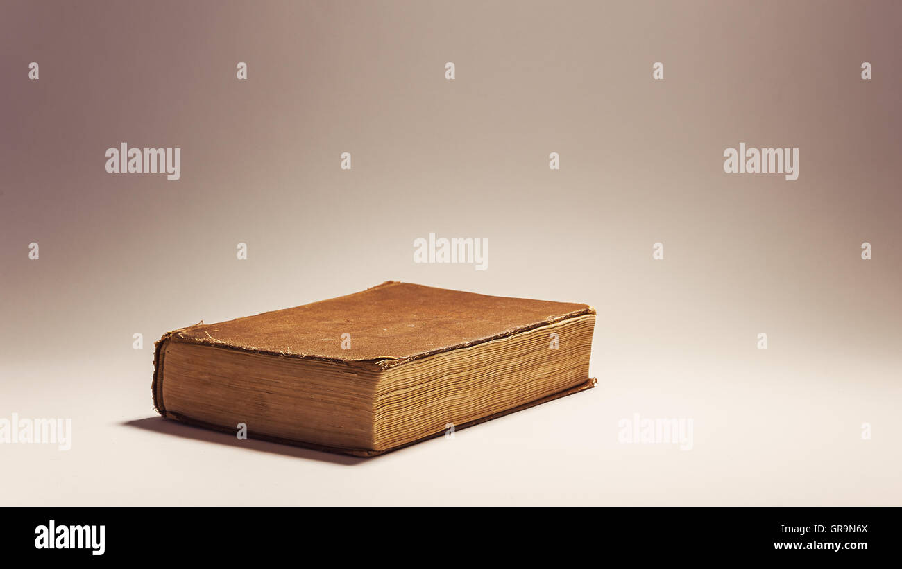 Composition conceptuelle au sujet de la lecture de livres, de vieux livre look rétro sur fond blanc. Photo Stock