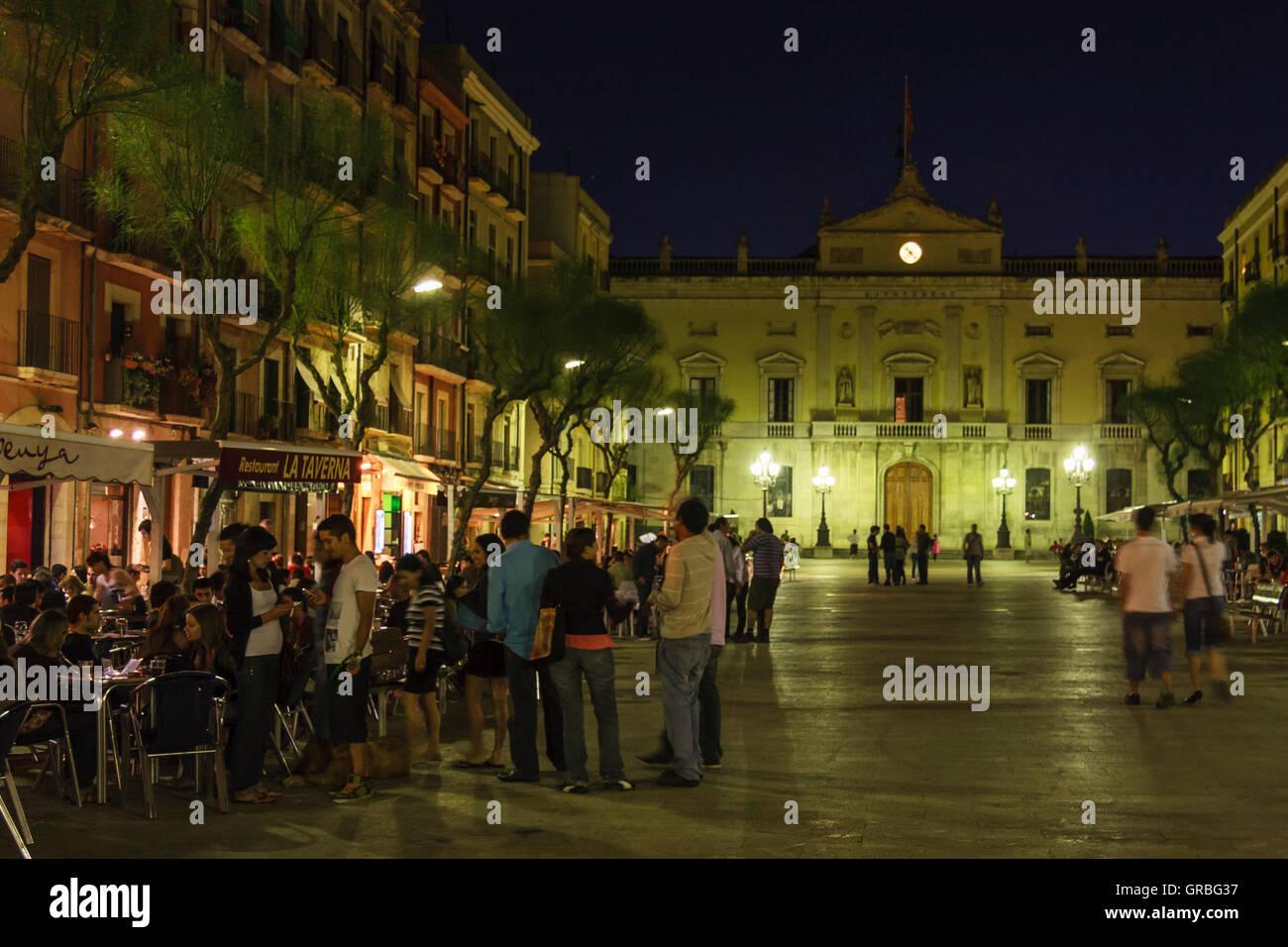 Les personnes bénéficiant de l'ambiance de fin de nuit en face de l'Hôtel de ville de Tarragone Photo Stock