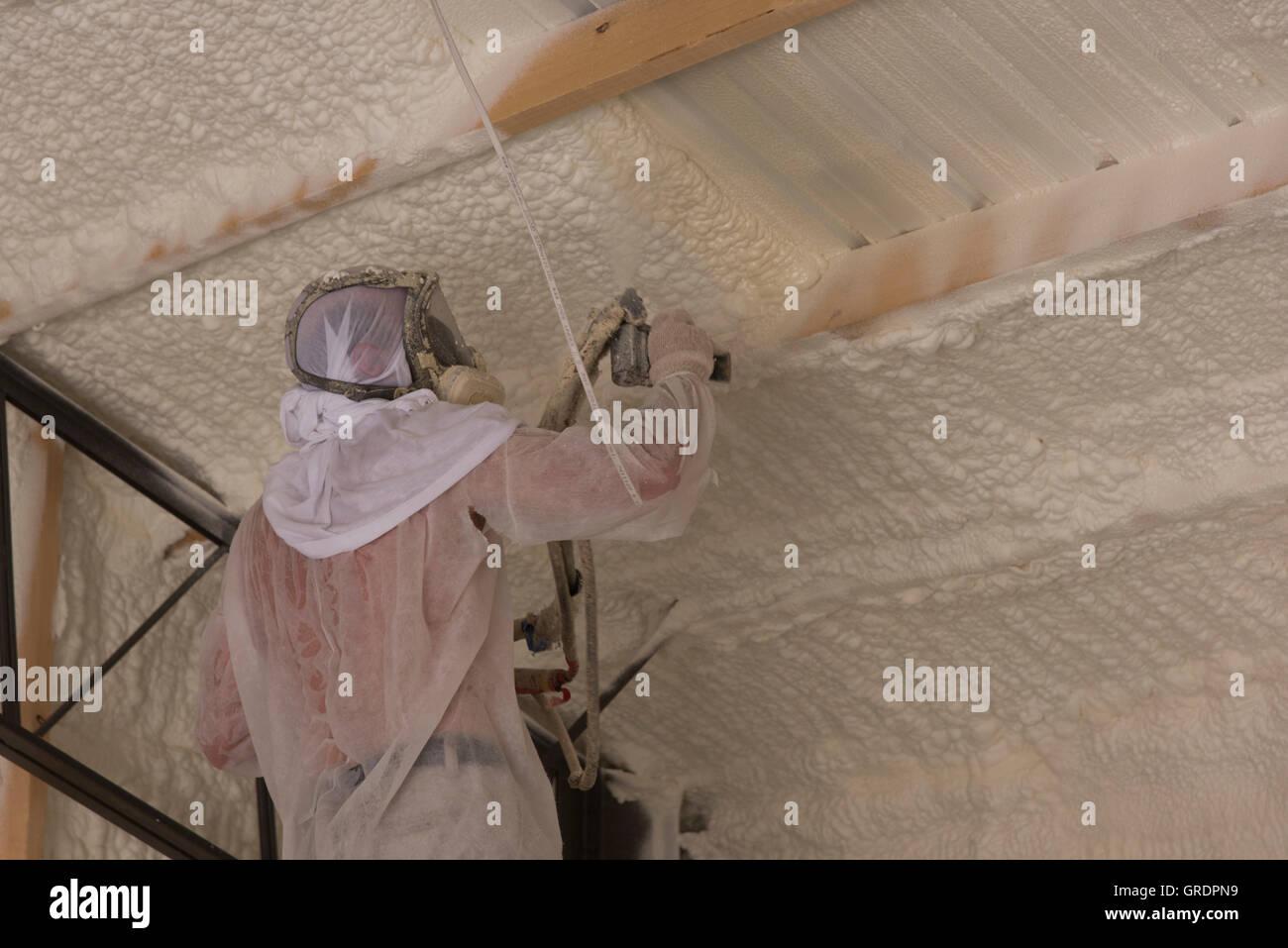 Un technicien s'applique à l'isolation de mousse à cellules ouvertes de l'intérieur d'une Photo Stock