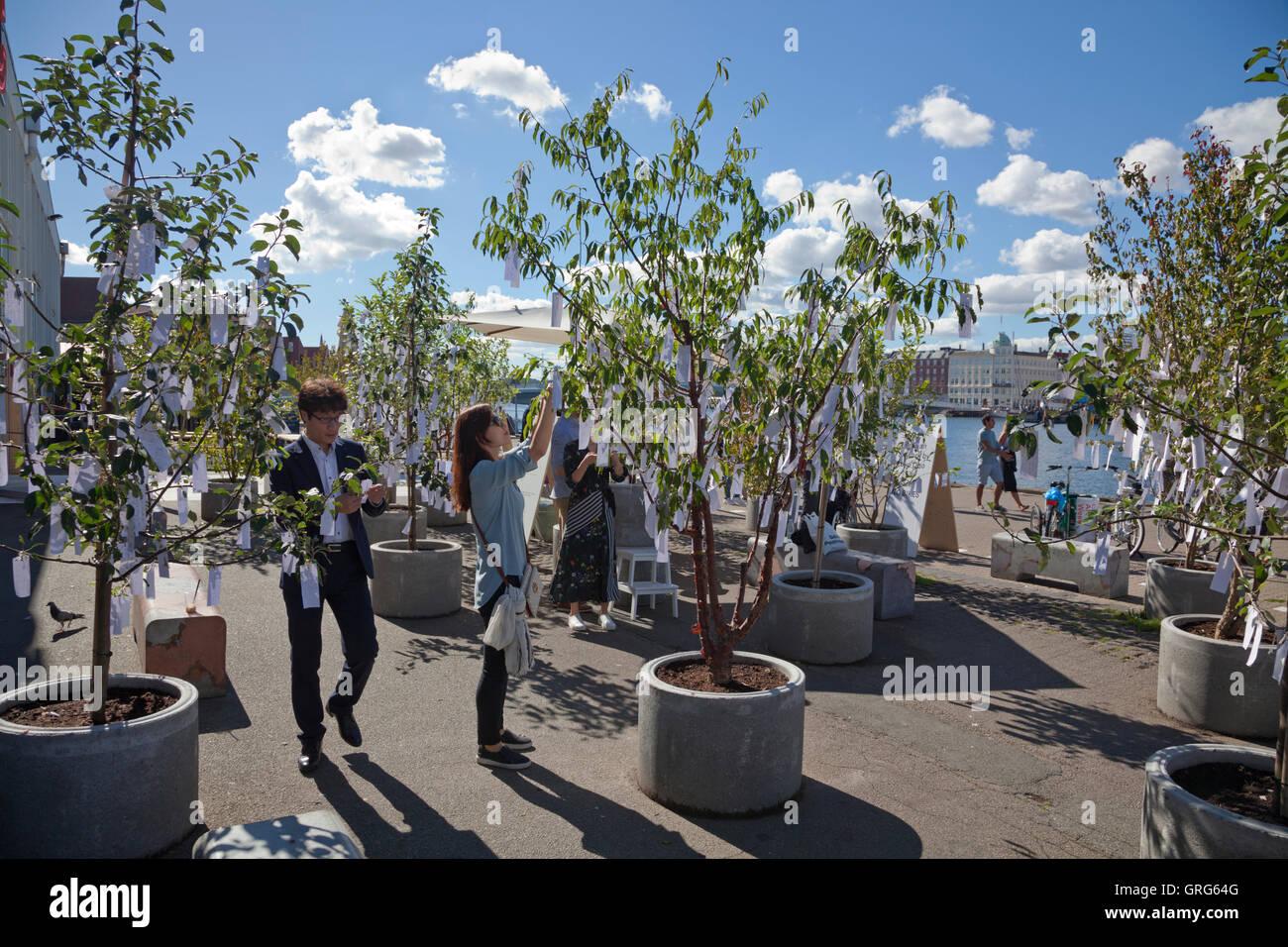 Les touristes à souhaits de lecture Arbre des désirs de Yoko Ono jardin à l'extérieur de l'entrepôt sur Papirøen, île de papier. Contemporain de Copenhague. Banque D'Images