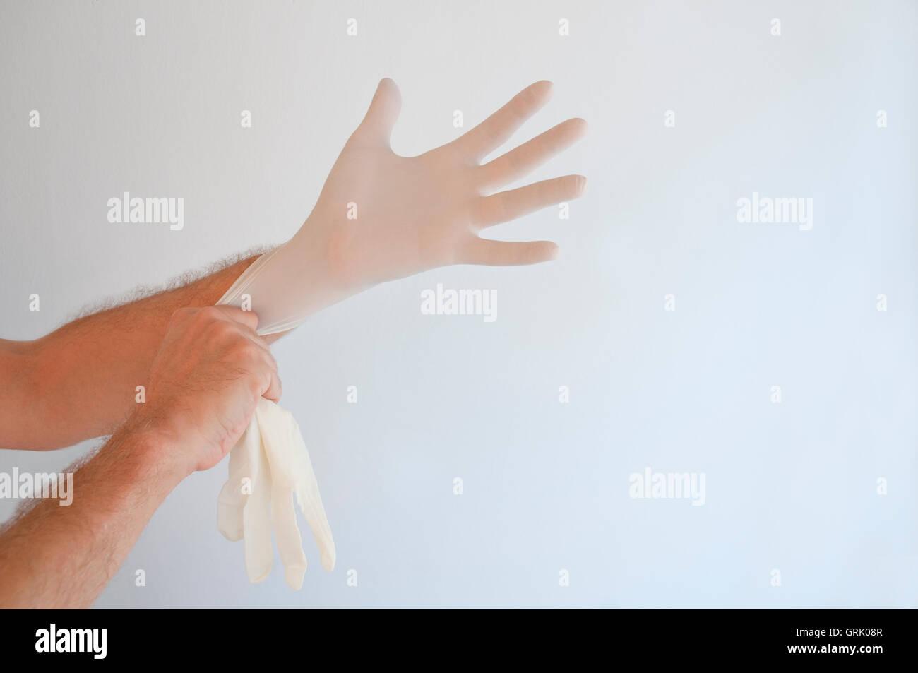 L'homme de mettre ses gants en latex. Banque D'Images