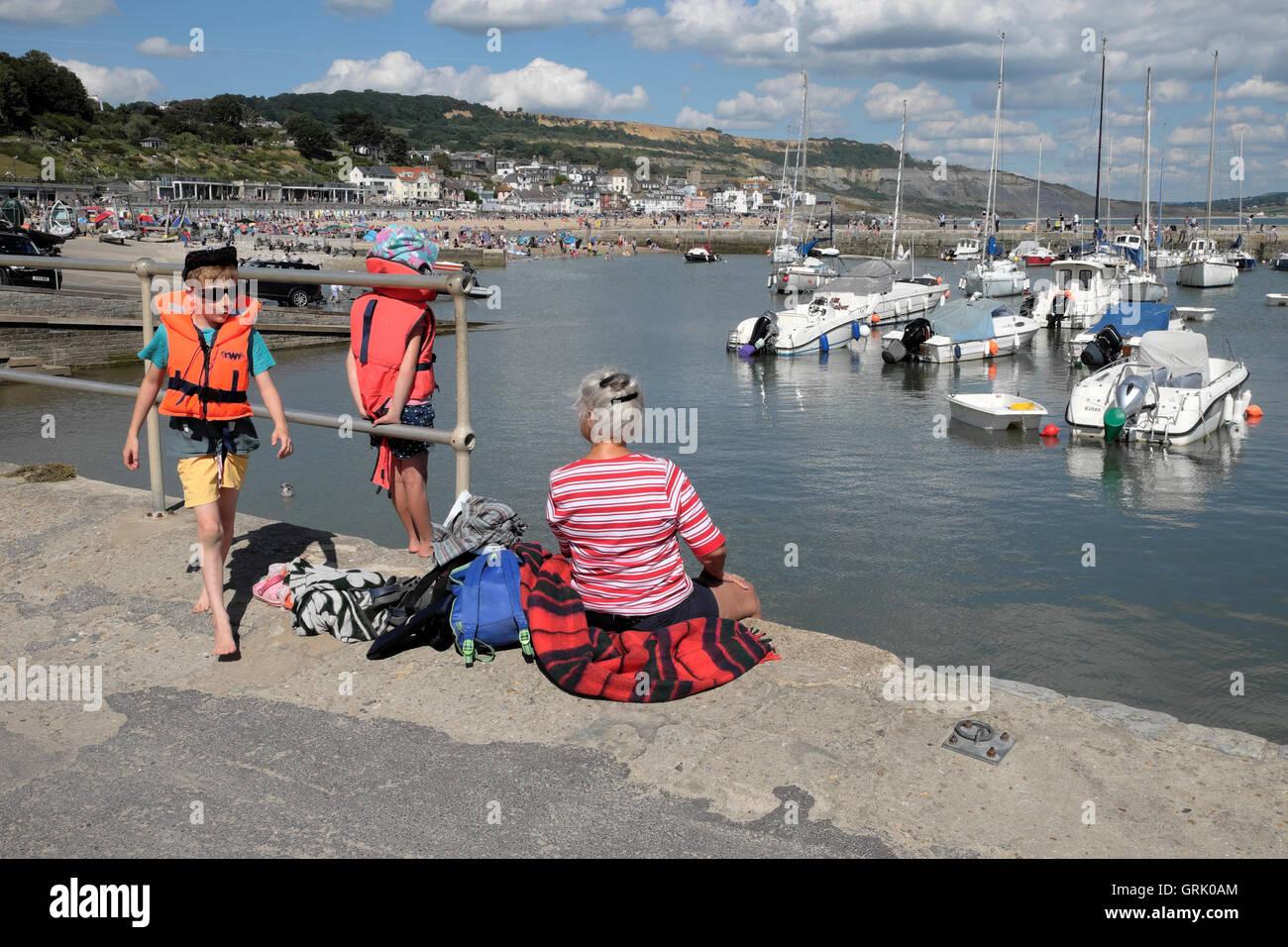 Une grand-mère et deux petits-enfants s'asseoir sur le quai du port le long de la Cobb à Lyme Regis Dorset England UK KATHY DEWITT Banque D'Images