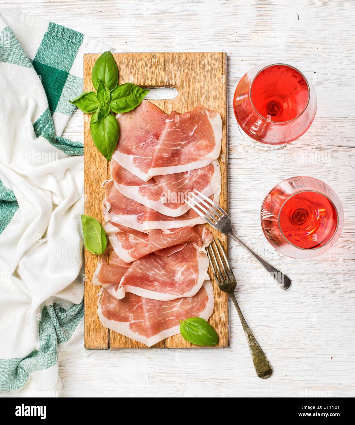 Tranches de jambon prosciutto di Parma et verres à vin rose Photo Stock