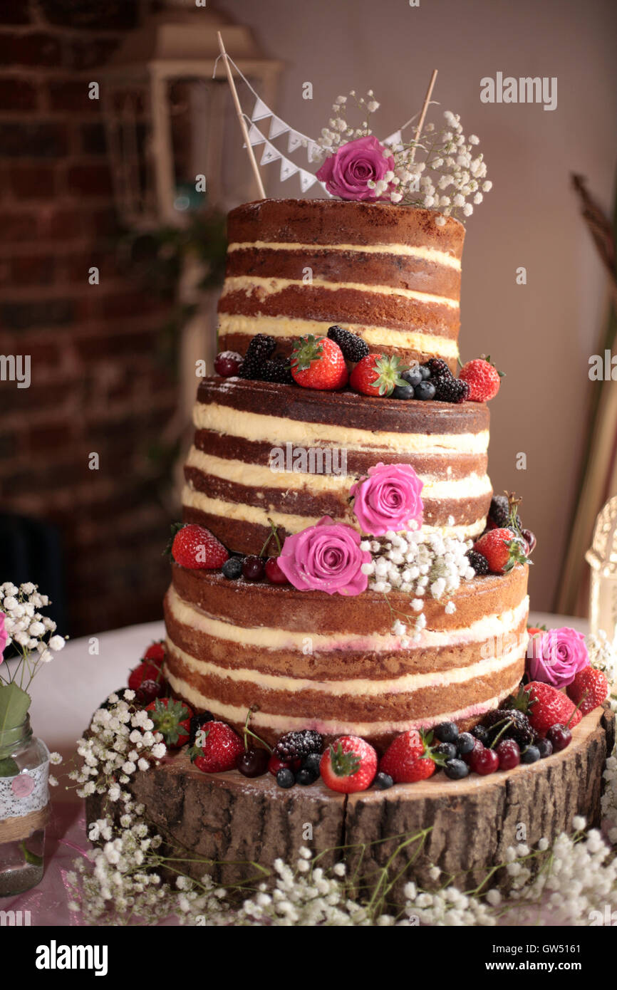 Un gâteau de mariage sens dessus dessous sur un journal avec les baies fraîches. Photo Stock