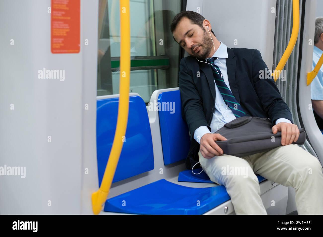 Tired businessman dormir sur le métro Photo Stock
