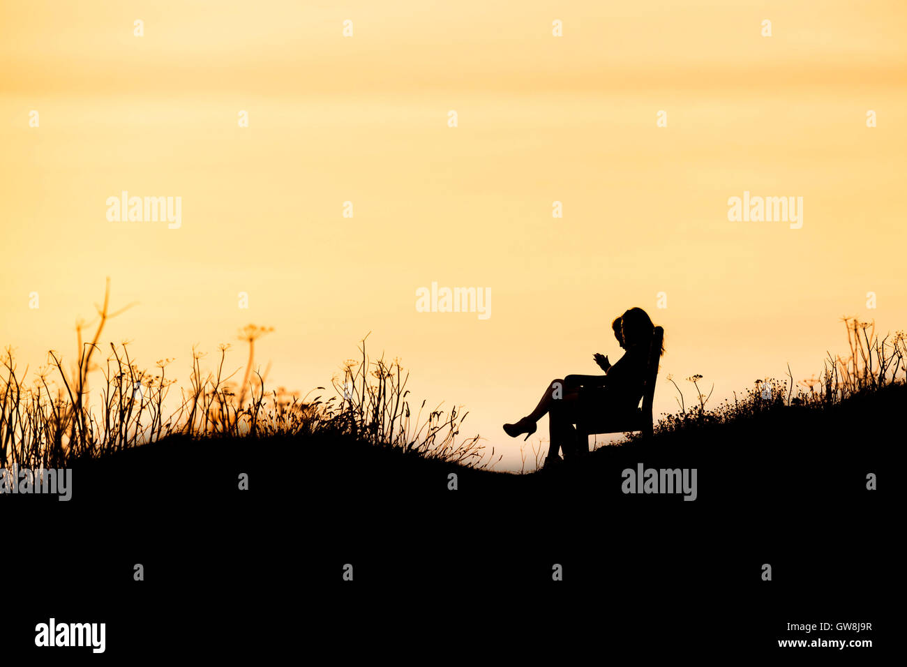 Les gens vu en silhouette lors d'un coucher de soleil intense. . Fistral Cornwall. Photo Stock
