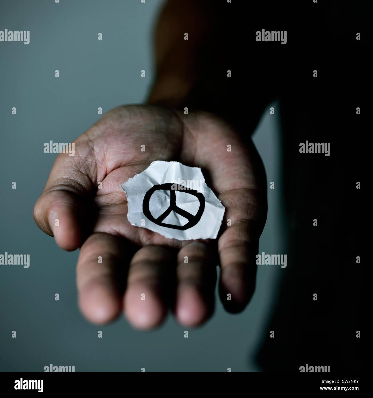 Libre d'un jeune homme avec un morceau de papier avec un symbole dessiné dans la paix, dans la paume de Photo Stock