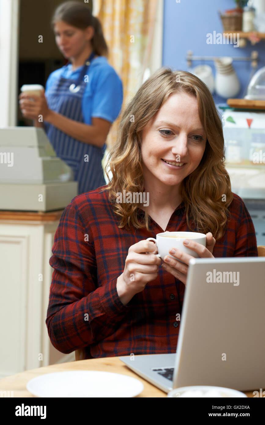 Femme dans un café à l'aide d'un ordinateur portable Photo Stock