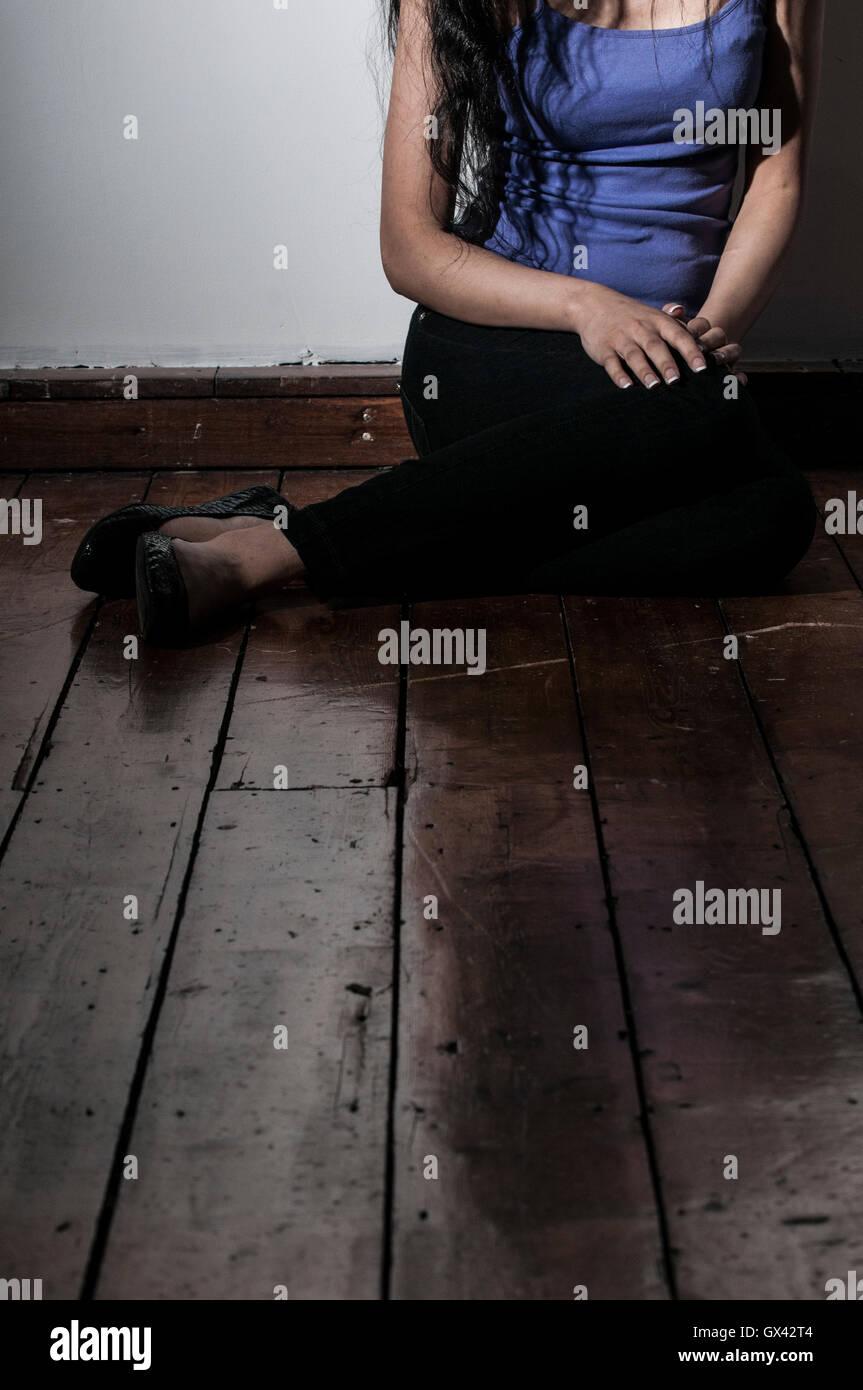 Femme seule assis sur le sol à l'intérieur Photo Stock
