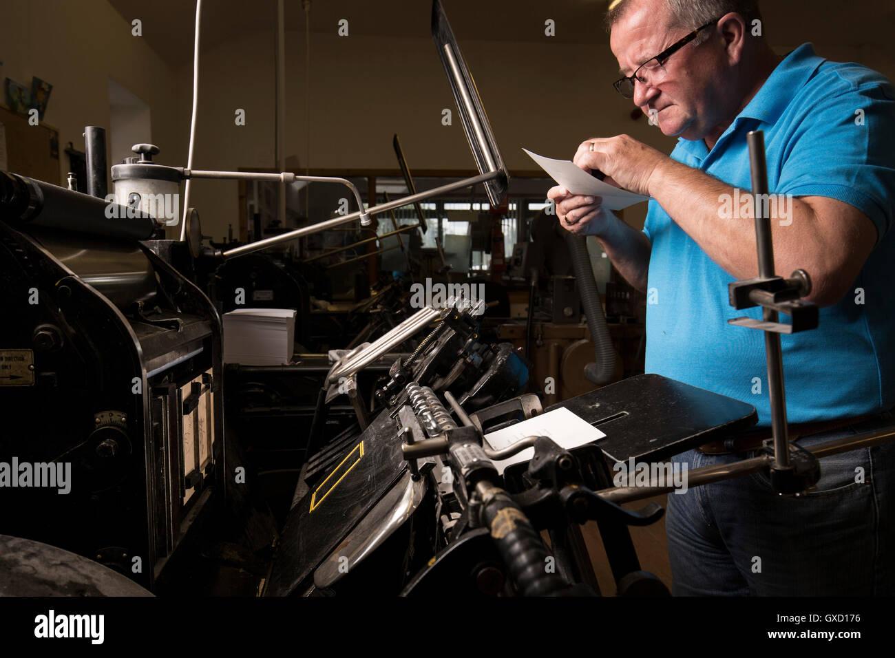 Mâle mature à l'inspection de l'imprimante pour l'impression papier impression machines dans l'atelier presse Banque D'Images