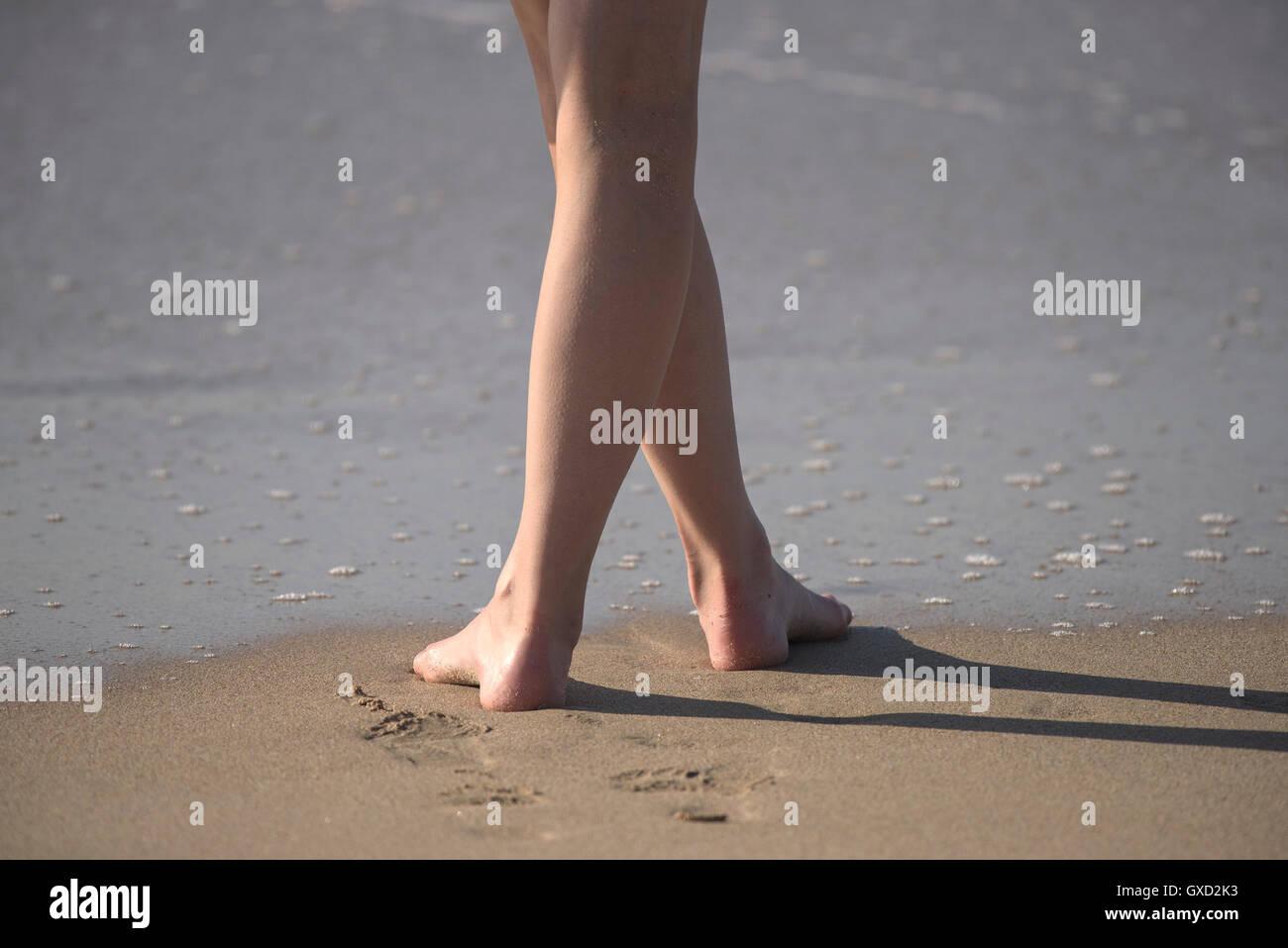 Les jambes nues sur une plage. Photo Stock