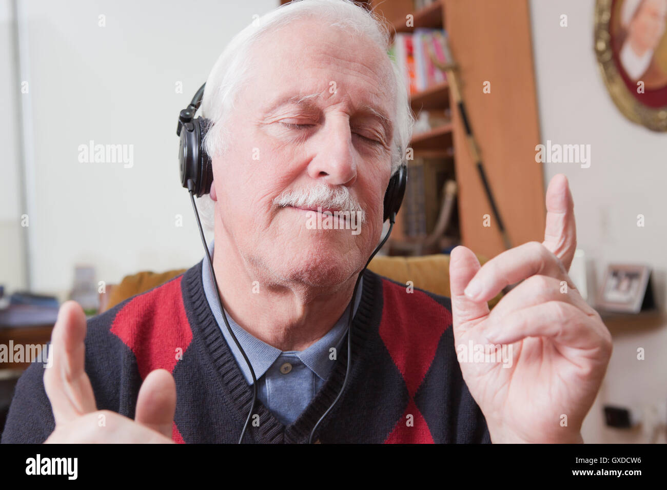 Senior man listening to music on écouteurs à la maison Banque D'Images