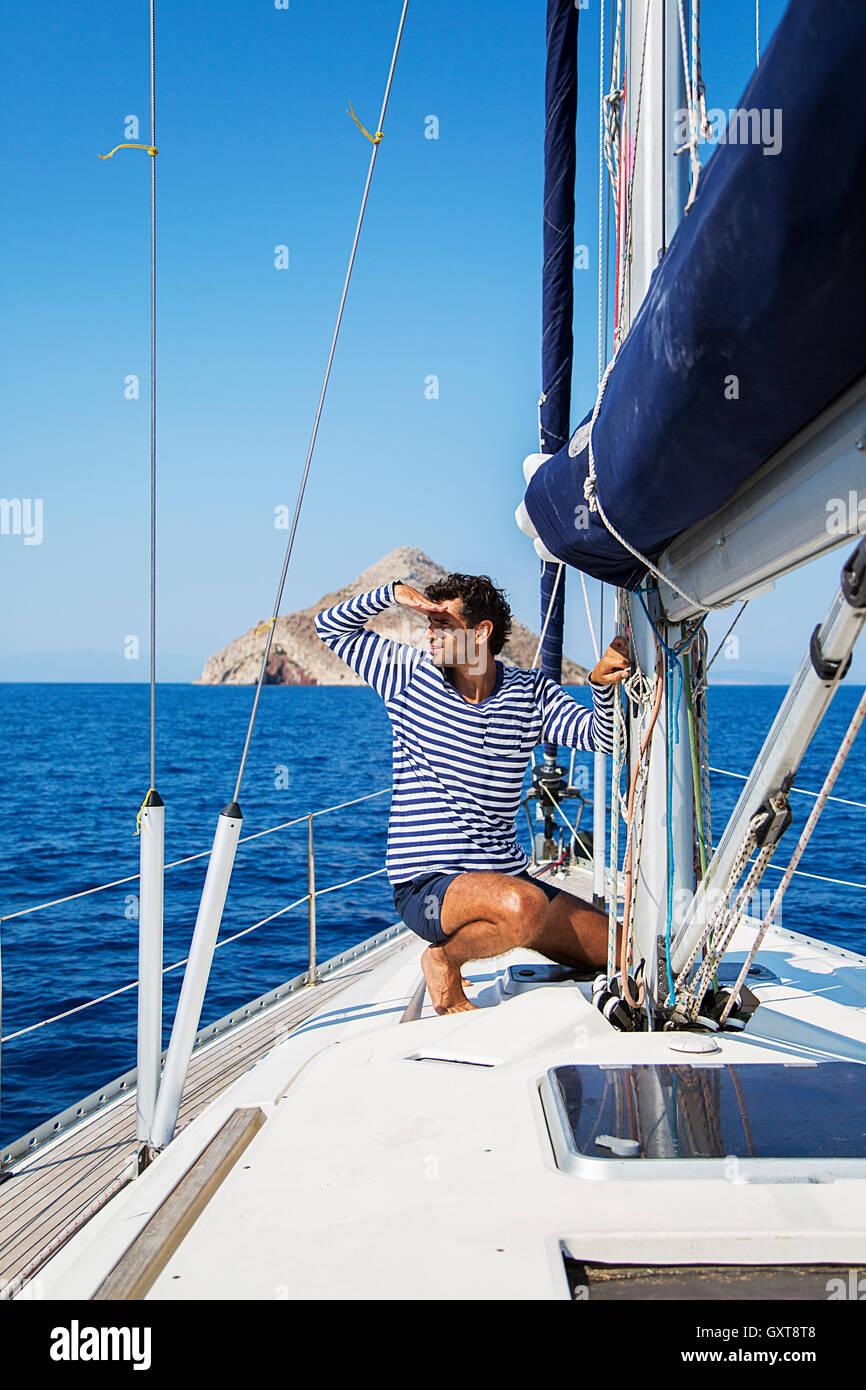 Jeune homme sur un voilier cherche dans la distance Photo Stock