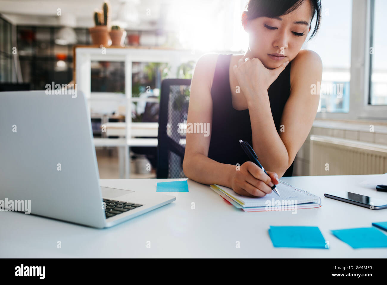 Shot of asian businesswoman writing notes sur le bloc-notes. La femme assise à son bureau avec ordinateur portable Photo Stock