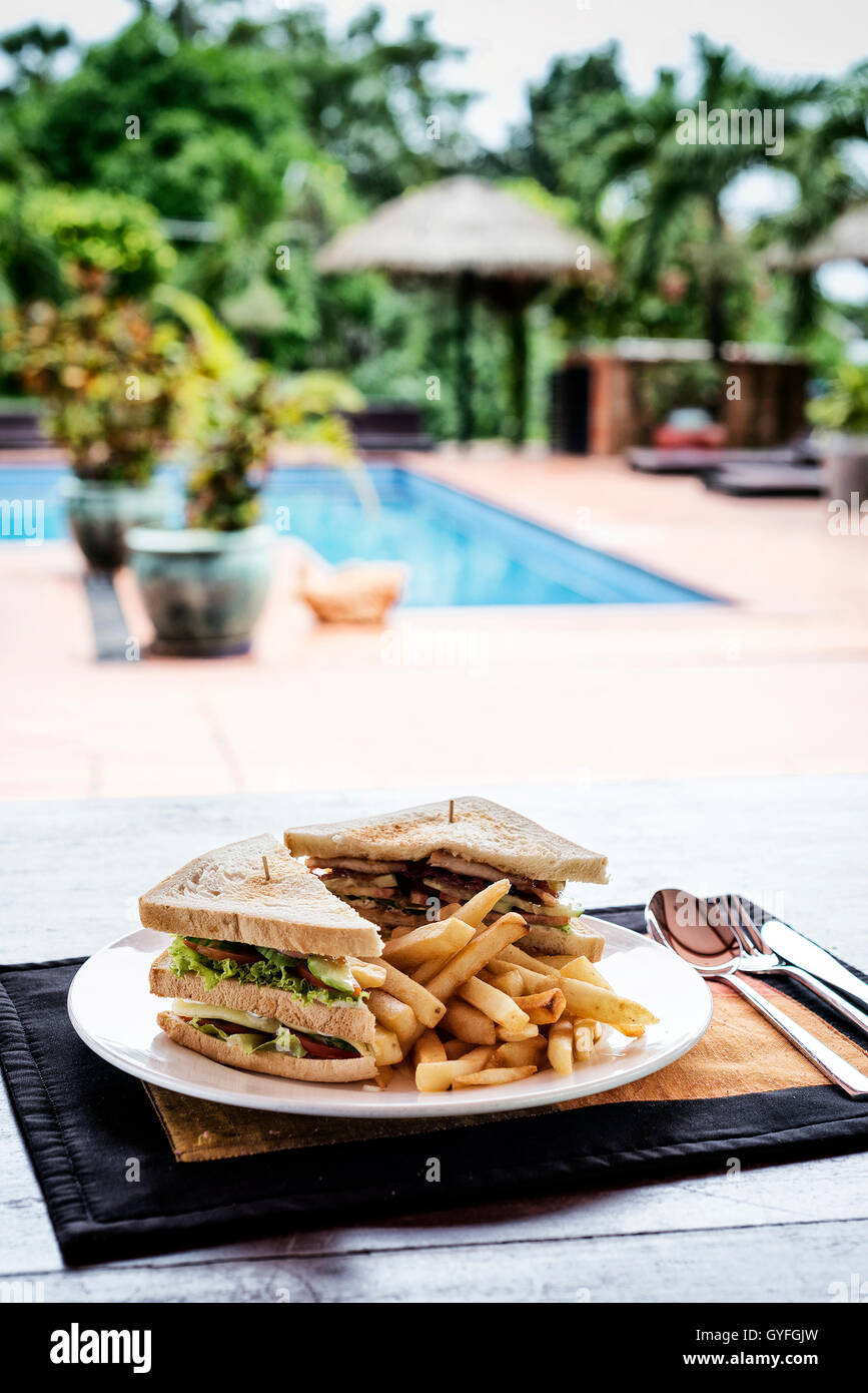Club sandwich snack avec les frites sur la plaque par piscine Photo Stock
