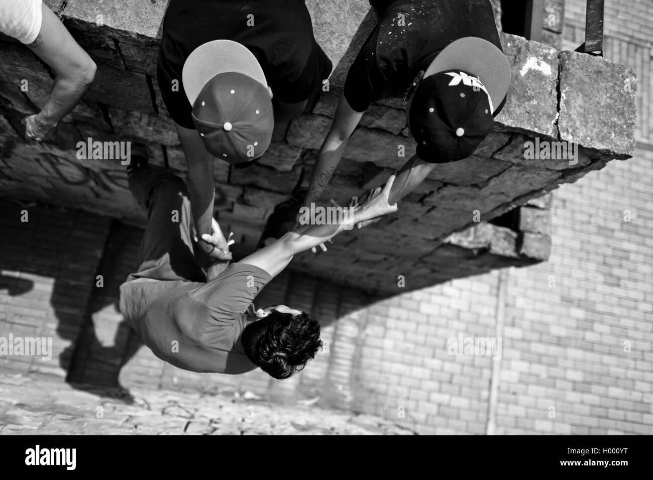 Un parkour runner, suspendu à ses copains' hands, grimpe sur le mur pendant une session de formation à Photo Stock