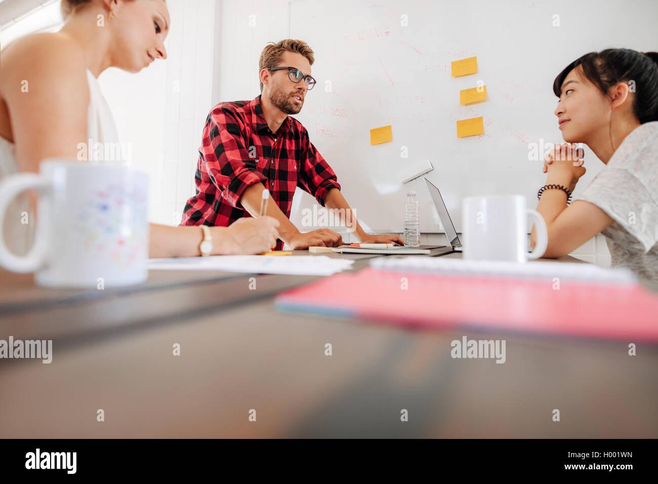 Groupe de discussion sur les cadres de démarrage de nouvelles idées d'affaires au cours d'une réunion en milieu de travail moderne. Employés autour d'une table de réunion Banque D'Images
