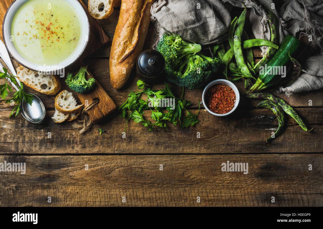 La courgette, le brocoli et les haricots verts dans un bol de soupe à la crème aux épices et la baguette Photo Stock