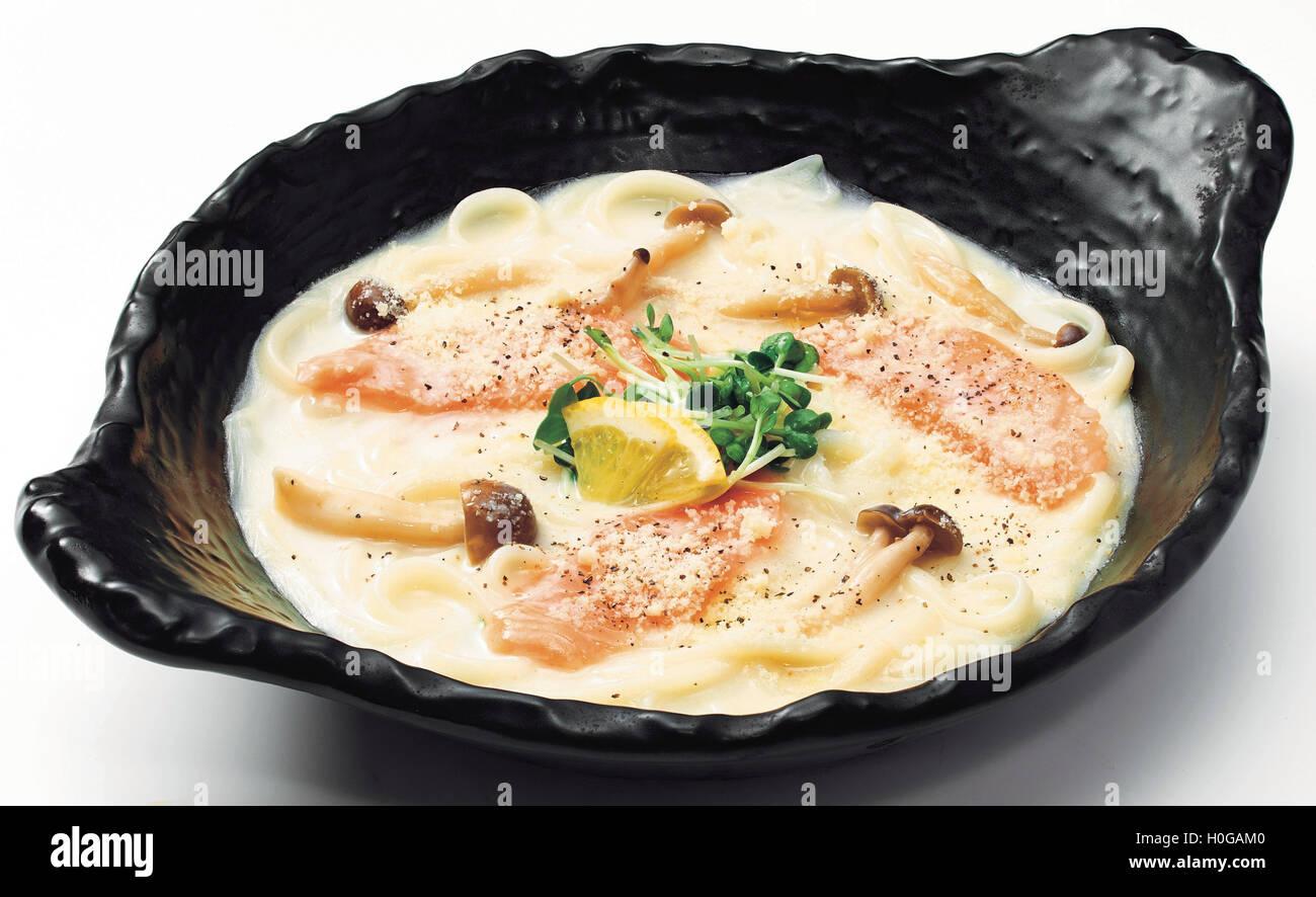 Nouilles Udon japonaise avec du saumon, champignons, citron et de germination en noir bol Photo Stock