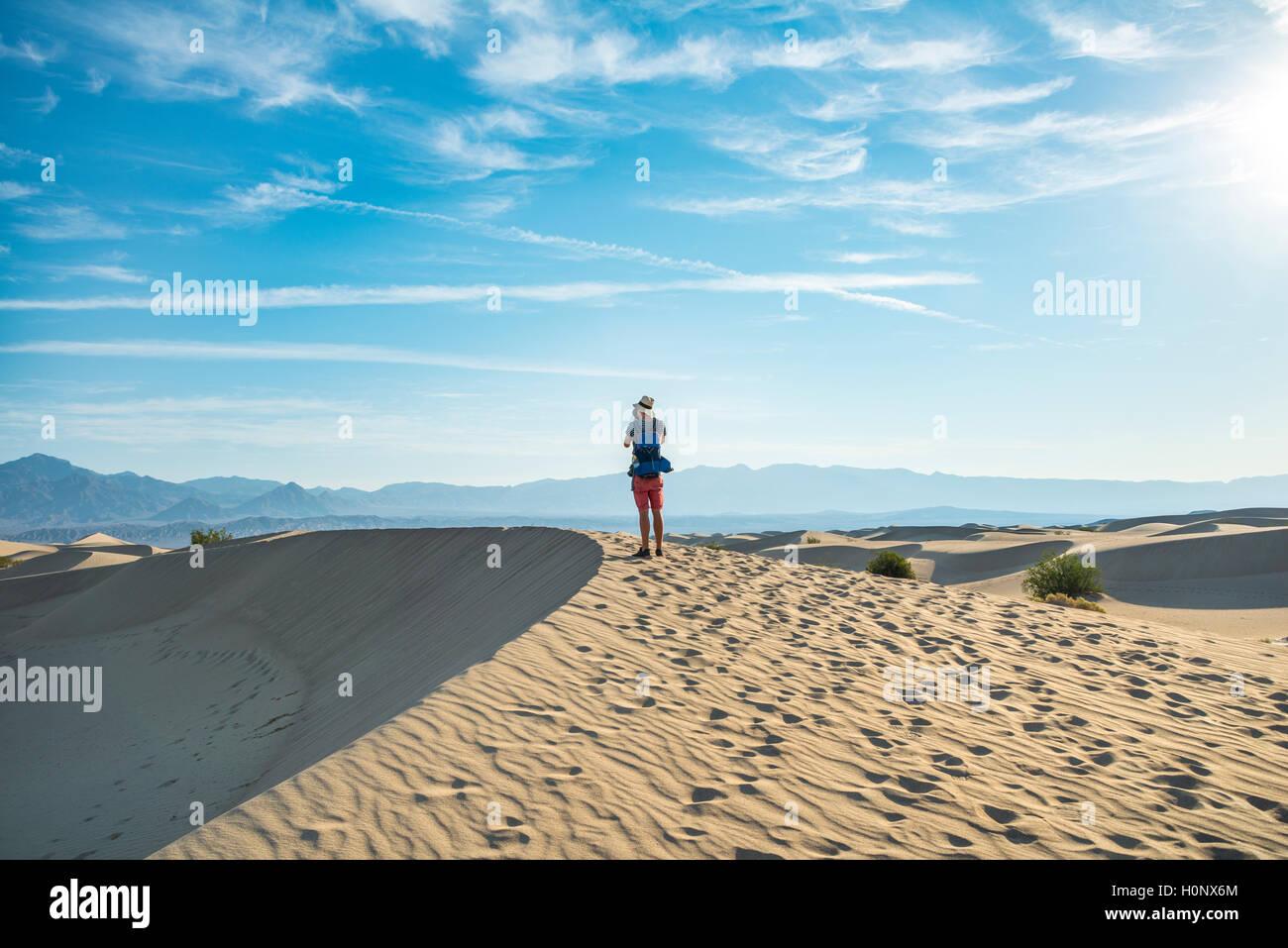 Young man photographing sand dunes, touristiques, de Mesquite Flat dunes de sable, contreforts de l'Amargosa Range derrière, la vallée de la mort Banque D'Images