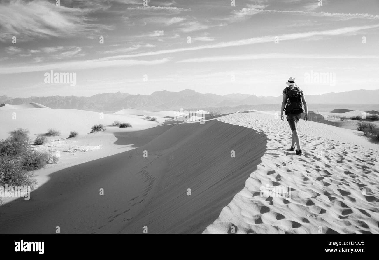 Jeune homme randonnée sur les dunes de sable, touristiques, de Mesquite Flat dunes de sable, contreforts de l'Amargosa Range derrière, la vallée de la mort Banque D'Images