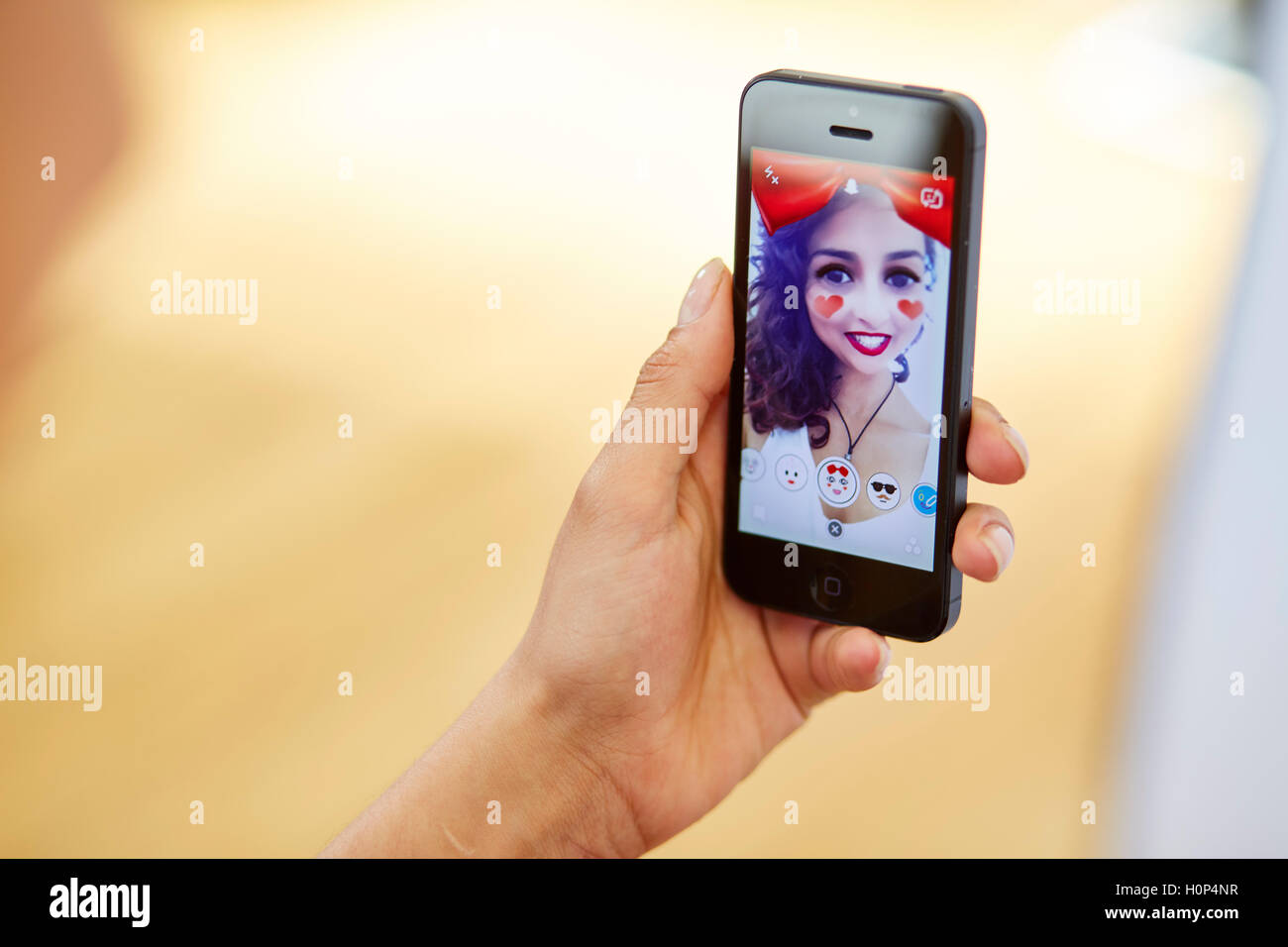 Girl Snapchat sur son iPhone app Photo Stock