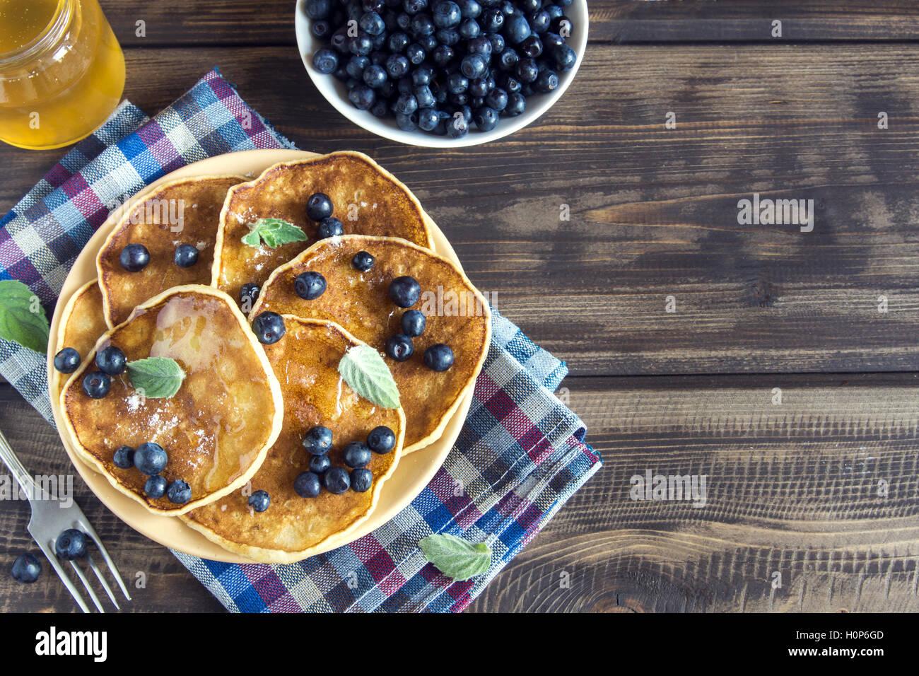 Des crêpes sur la plaque avec des bleuets, de la menthe et du miel pour le petit déjeuner fait maison Photo Stock