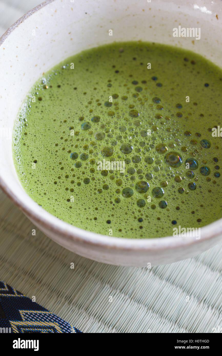 Thé vert japonais Matcha dans un bol en céramique traditionnelle ou chawan tourné avec l'accent Photo Stock